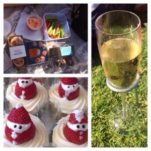 Glass of champagne stuck in grass, santa clause cupcakes and finger snacks.