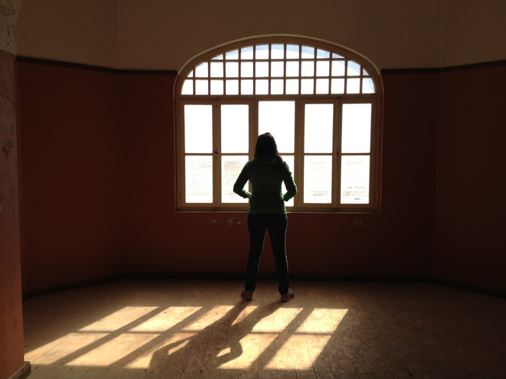 Silhouette of girl in a window frame in empty house.