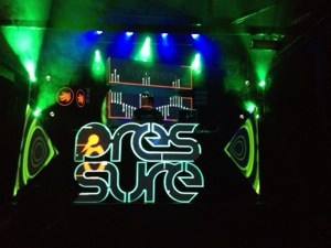 DJ in DJ box with green lights and the word Pressure outlined in blue in front of him.