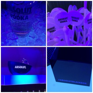 Vodka bottle on ice, white swizzle sticks, absolut vodka bucket, black box on blue counter