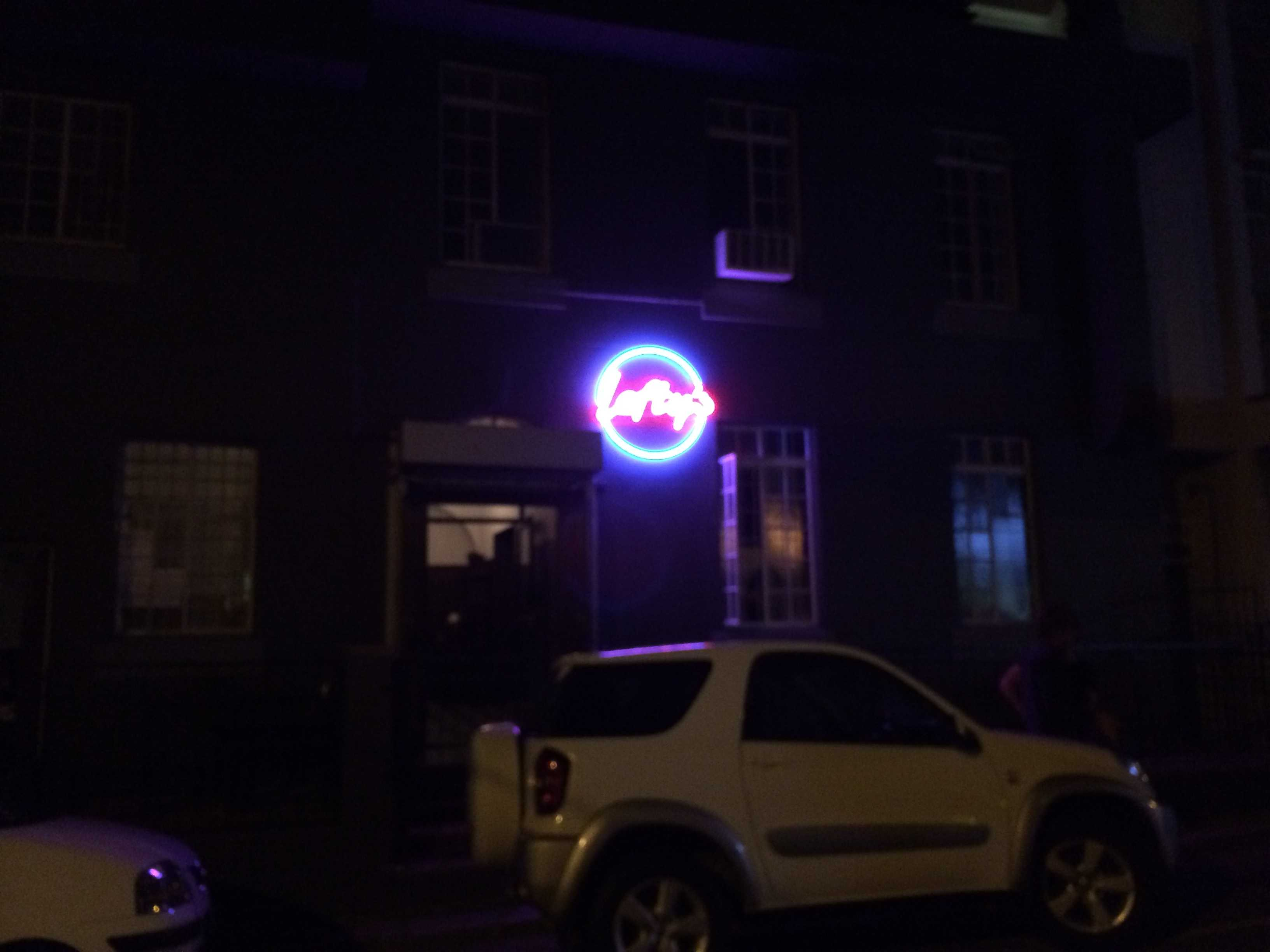 Blue and Pink Florescent Sign above dark door way