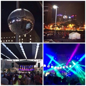 Giant disco ball in city, disco ball in city, stage with mountain behind it, turquoise lazer lights at festival