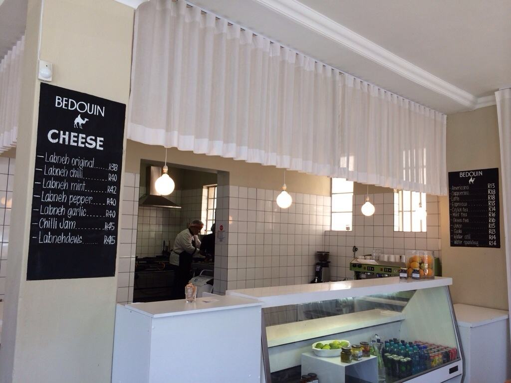 Deli counter with white curtain hanging above with black chalk board menu next to counter.