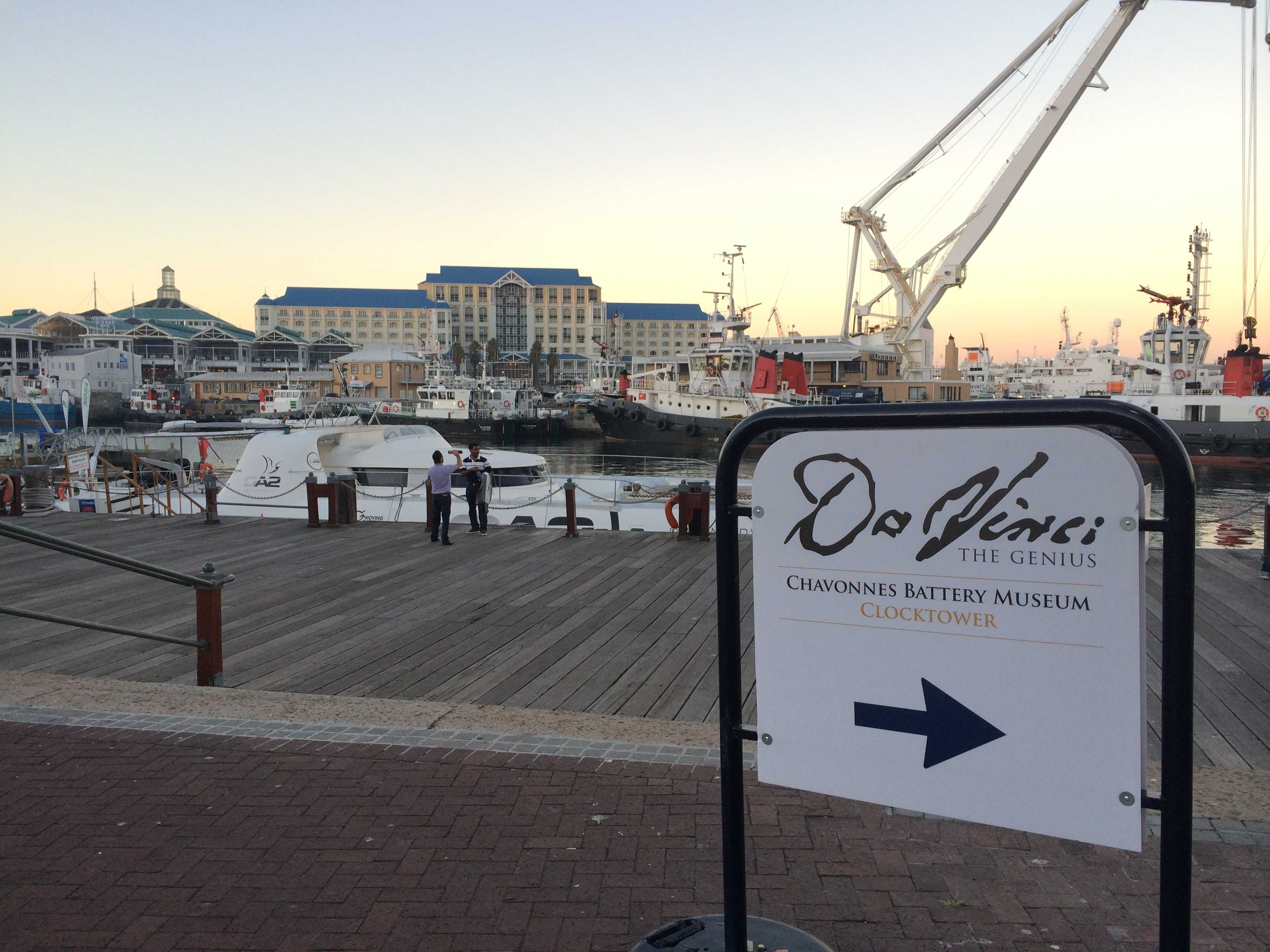 Victoria and Alfred Hotel across the dock at dusk with crane and white sign