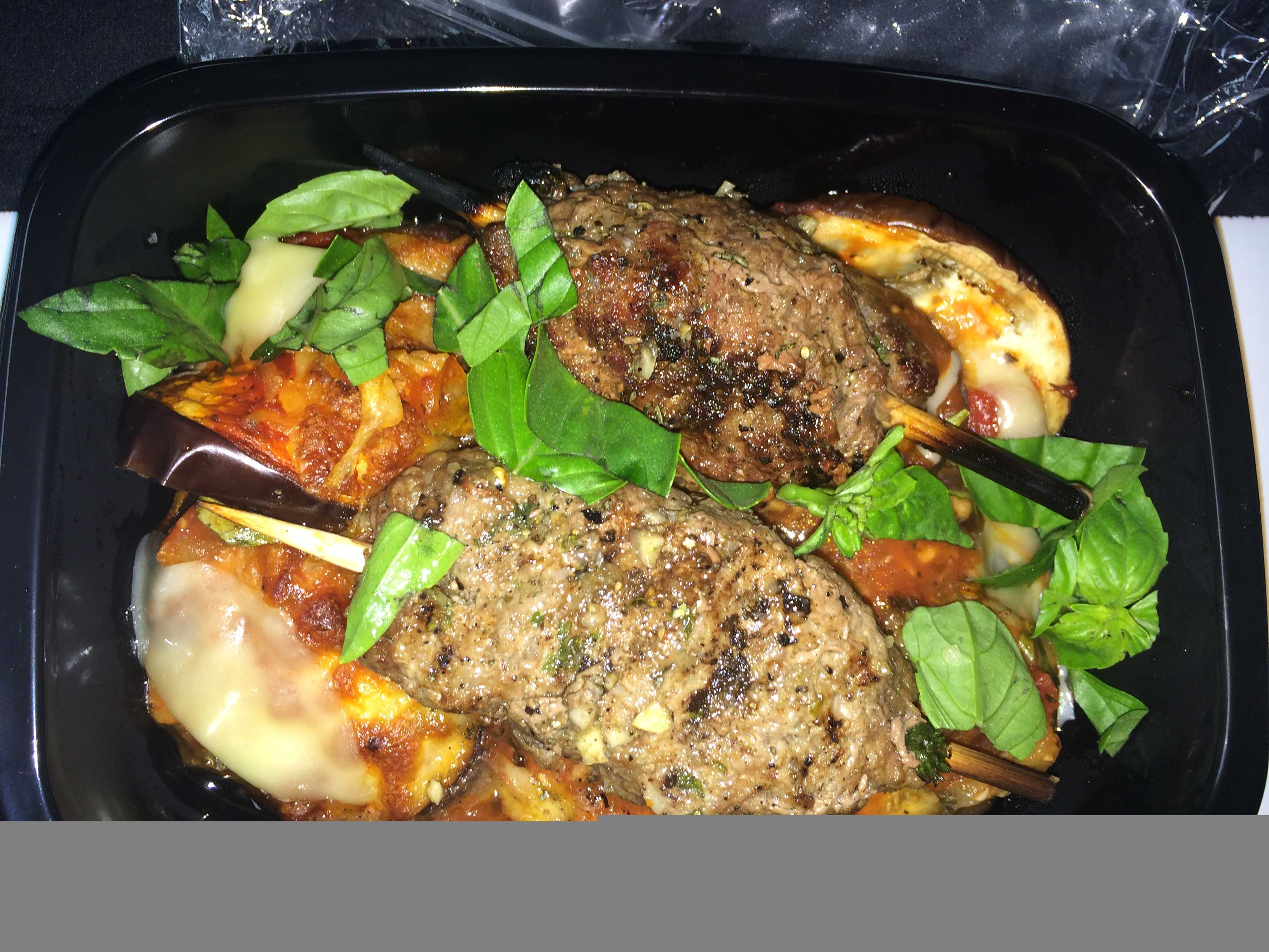 beef koftas on eggplant with fresh basil in black tub