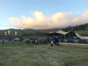Outdoor stage in grassy field in mountains
