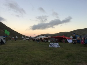 Food stalls in grassy field under cloudy sunset sky