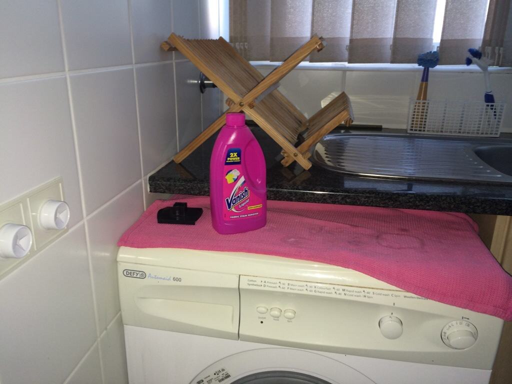 Pink Vanish bottle on top of washing machine with dish rack and pink dish cloth