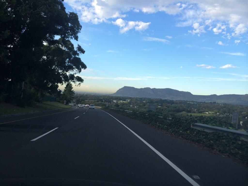 tarred road heading towards mountain next to tree and valley