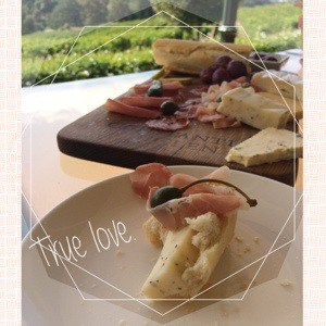 cheese, ham, capers on wooden serving board at green vineyards