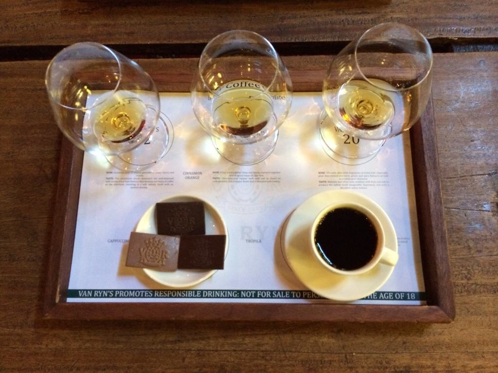 3 glasses with golden brandy, 3 chocolates and a cup of black coffee on a white paper on a wooden tray