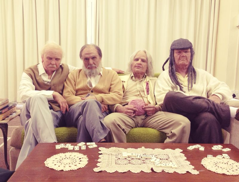 four grandpas sitting on a couch behind a coffee table with doilies on