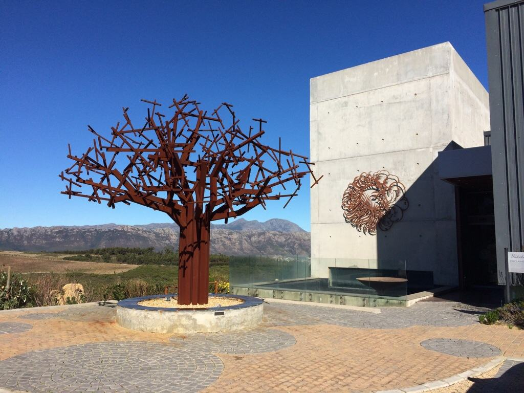 bronze baobab tree next to cement grey building on hilltop with blue skies