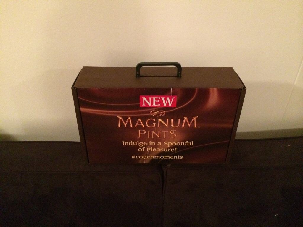 brown cardboard box with magnum written in gold on black couch