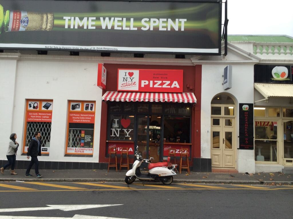 red sign of a pizza shop on tarmac roadwith scooter parked outside with red striped cover