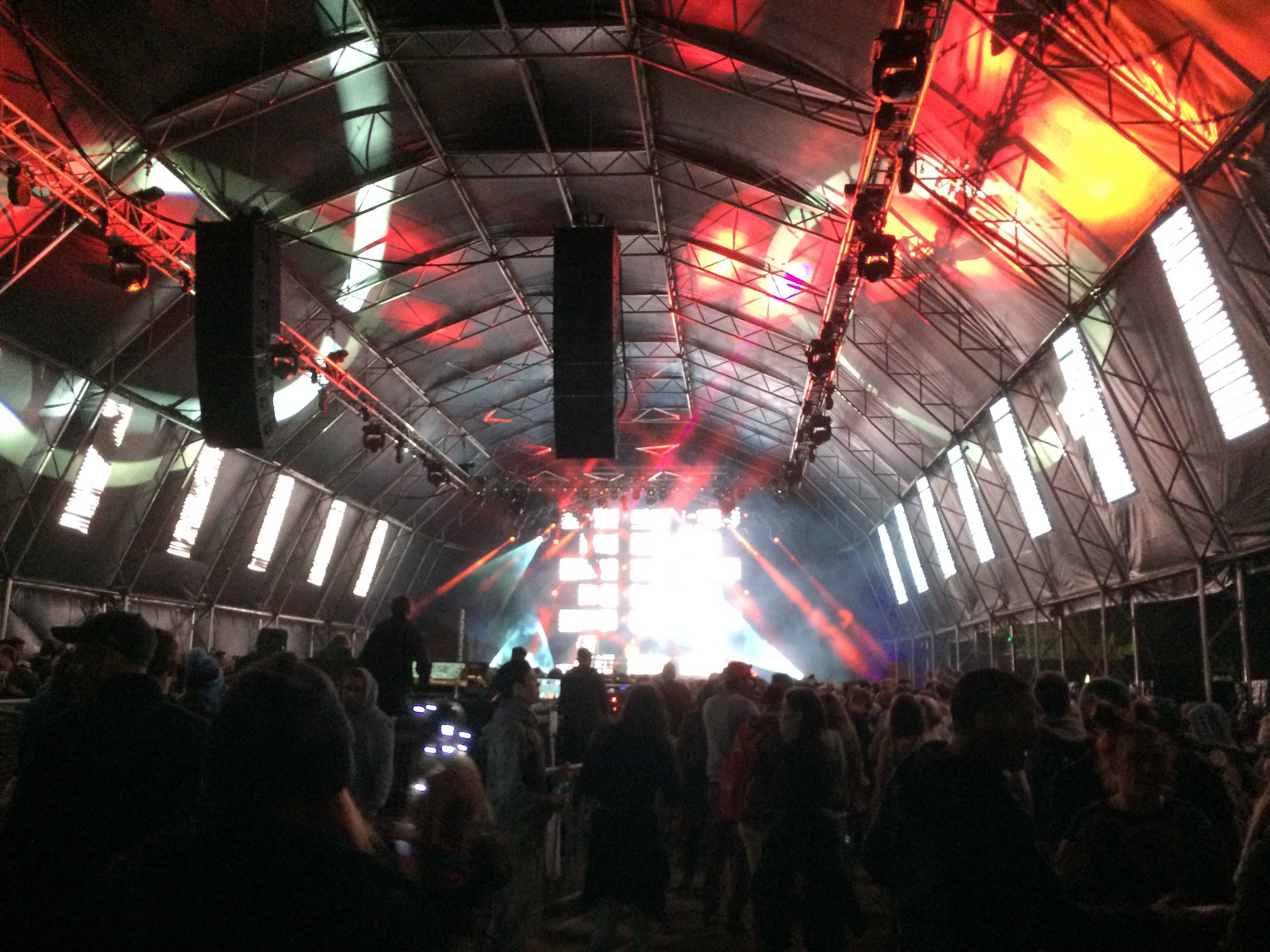 giant festival tent with lights projected on the walls and LED stage lights