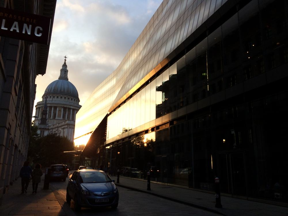 st paul's cathedral peeking between two buildings with the sunset reflecting on the glass