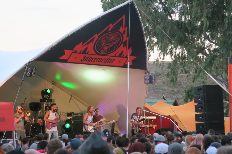 band playing on a triangle shaped stage under a tree